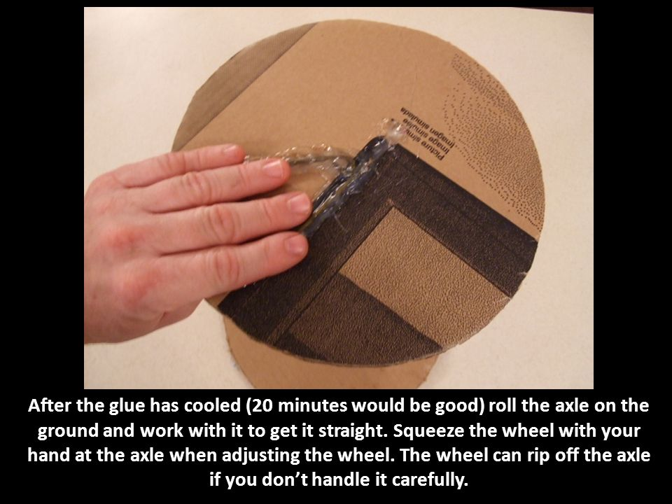 After the glue has cooled (20 minutes would be good) roll the axle on the ground and work with it to get it straight. Squeeze the wheel with your hand