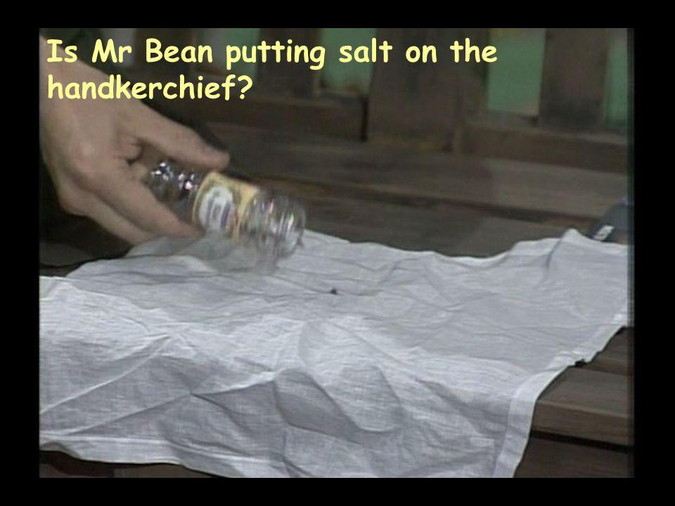 Is Mr Bean putting salt on the handkerchief?