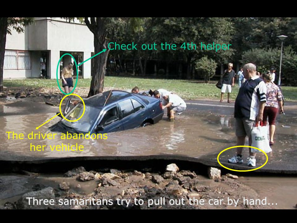 Three samaritans try to pull out the car by hand... The driver abandons her vehicle Check out the 4th helper
