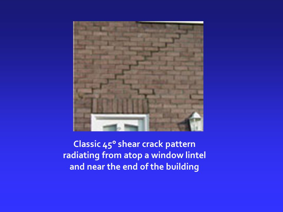 Classic 45° shear crack pattern radiating from atop a window lintel and near the end of the building