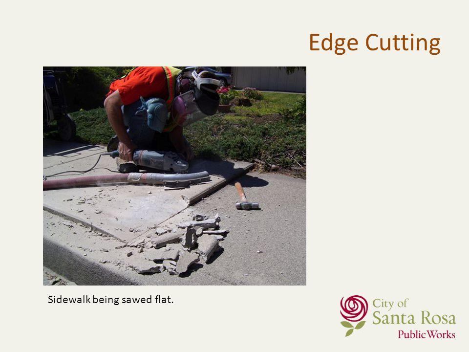 Sidewalk being sawed flat. Edge Cutting