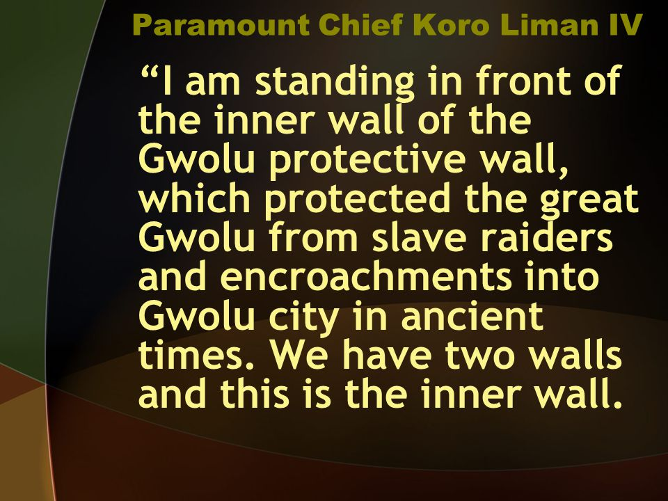 Paramount Chief Koro Liman IV I am standing in front of the inner wall of the Gwolu protective wall, which protected the great Gwolu from slave raiders and encroachments into Gwolu city in ancient times.