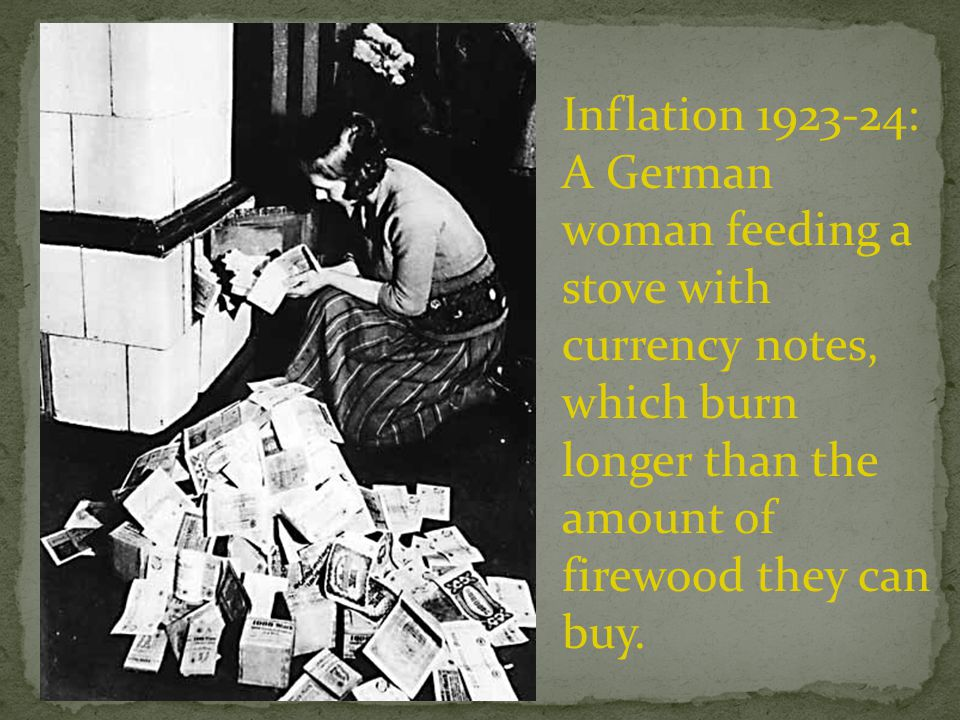 Inflation 1923-24: A German woman feeding a stove with currency notes, which burn longer than the amount of firewood they can buy.