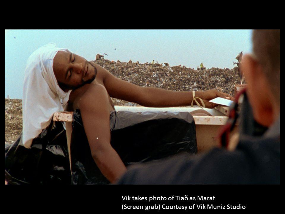 Vik takes photo of Tiaõ as Marat (Screen grab) Courtesy of Vik Muniz Studio