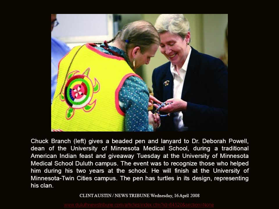 Chuck Branch (left) gives a beaded pen and lanyard to Dr.
