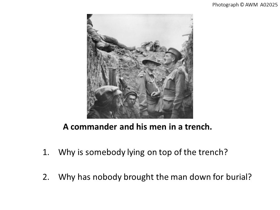 A commander and his men in a trench. 1.Why is somebody lying on top of the trench.