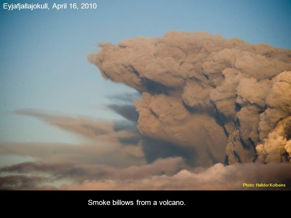 A small plane (upper left) flies past smoke and ash billowing from a volcano in Eyjafjallajokul, Iceland.