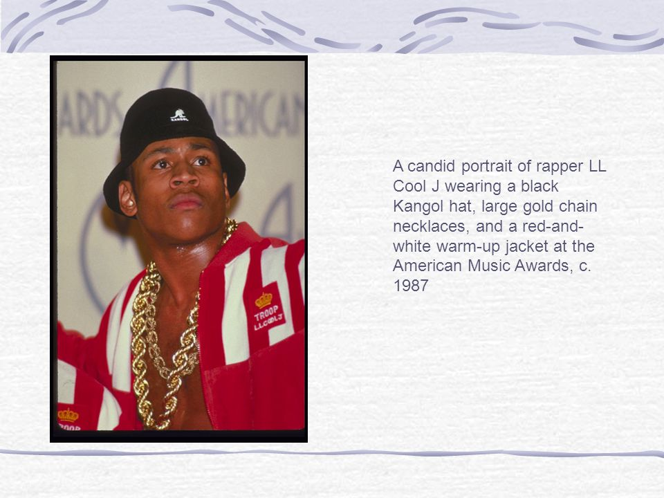 A candid portrait of rapper LL Cool J wearing a black Kangol hat, large gold chain necklaces, and a red-and- white warm-up jacket at the American Music Awards, c.