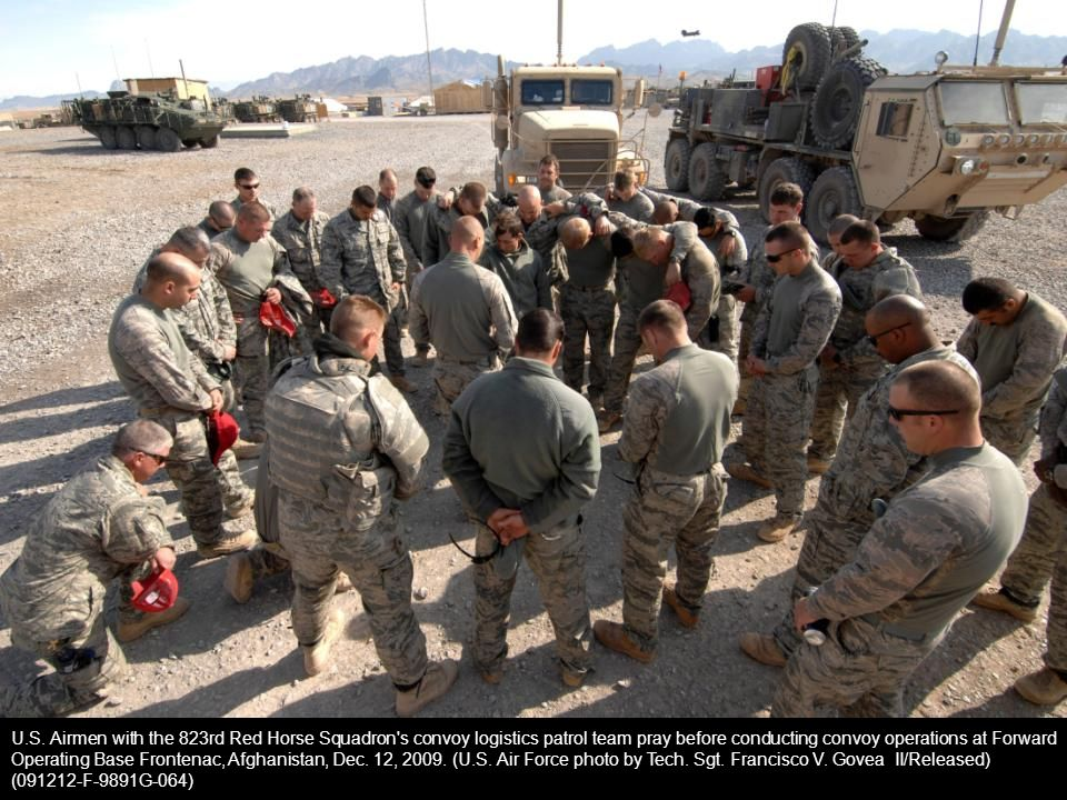 U.S. Airmen with the 823rd Red Horse Squadron's convoy logistics patrol team pray before conducting convoy operations at Forward Operating Base Fronte