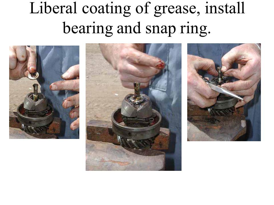 Liberal coating of grease, install bearing and snap ring.