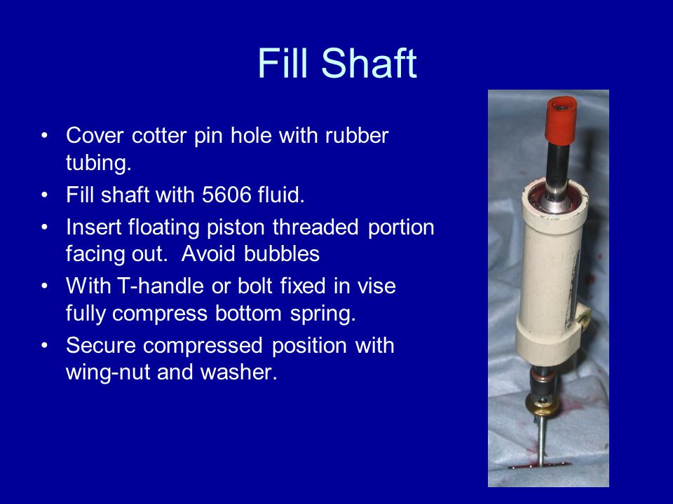 Fill Shaft Cover cotter pin hole with rubber tubing. Fill shaft with 5606 fluid. Insert floating piston threaded portion facing out. Avoid bubbles Wit