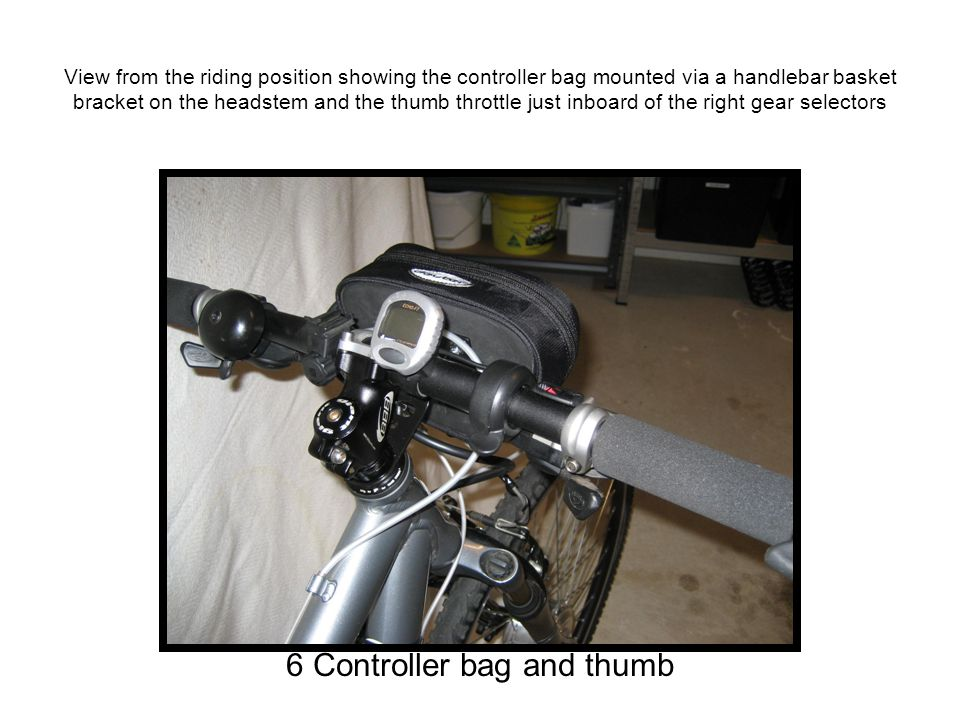 View from the riding position showing the controller bag mounted via a handlebar basket bracket on the headstem and the thumb throttle just inboard of the right gear selectors