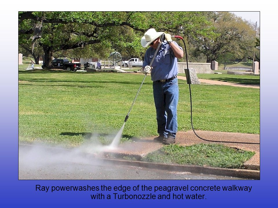 Ray powerwashes the edge of the peagravel concrete walkway with a Turbonozzle and hot water.
