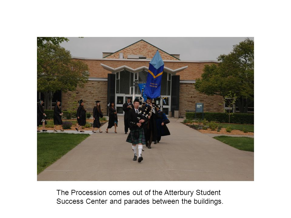 The Procession comes out of the Atterbury Student Success Center and parades between the buildings.