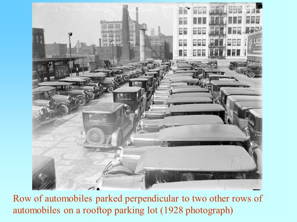 Row of automobiles parked perpendicular to two other rows of automobiles on a rooftop parking lot (1928 photograph)