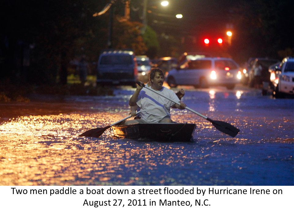 Two men paddle a boat down a street flooded by Hurricane Irene on August 27, 2011 in Manteo, N.C.