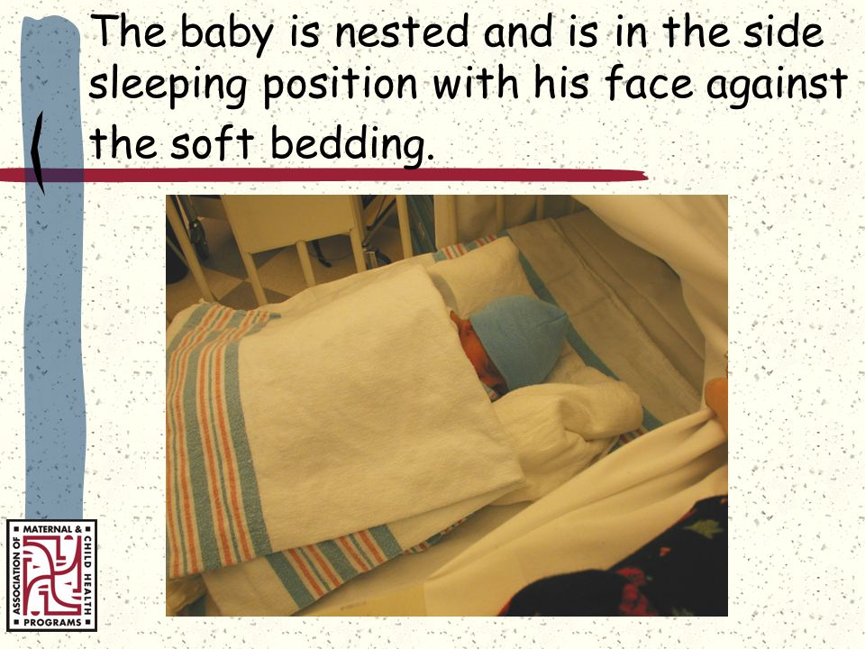 The baby is nested and is in the side sleeping position with his face against the soft bedding.
