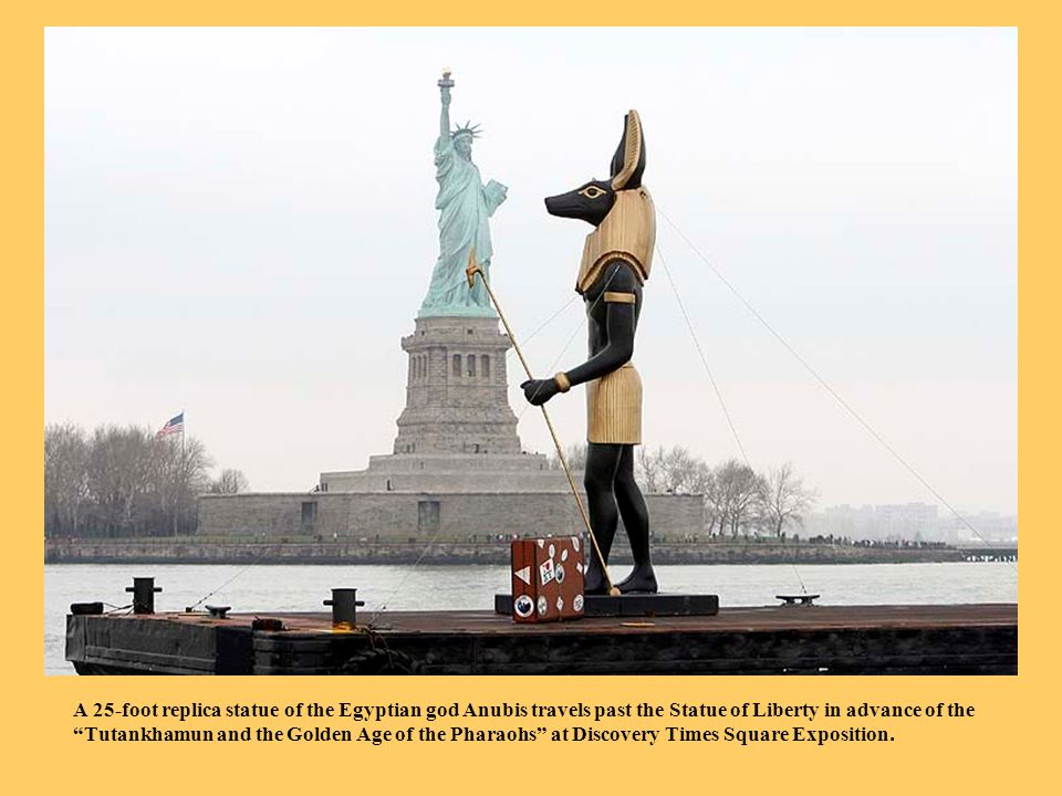 A 25-foot replica statue of the Egyptian god Anubis travels past the Statue of Liberty in advance of the Tutankhamun and the Golden Age of the Pharaohs at Discovery Times Square Exposition.
