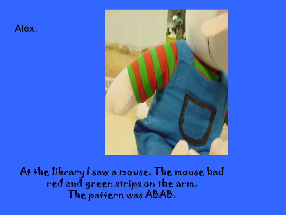 At the library I saw a mouse.The mouse had red and green strips on the arm.