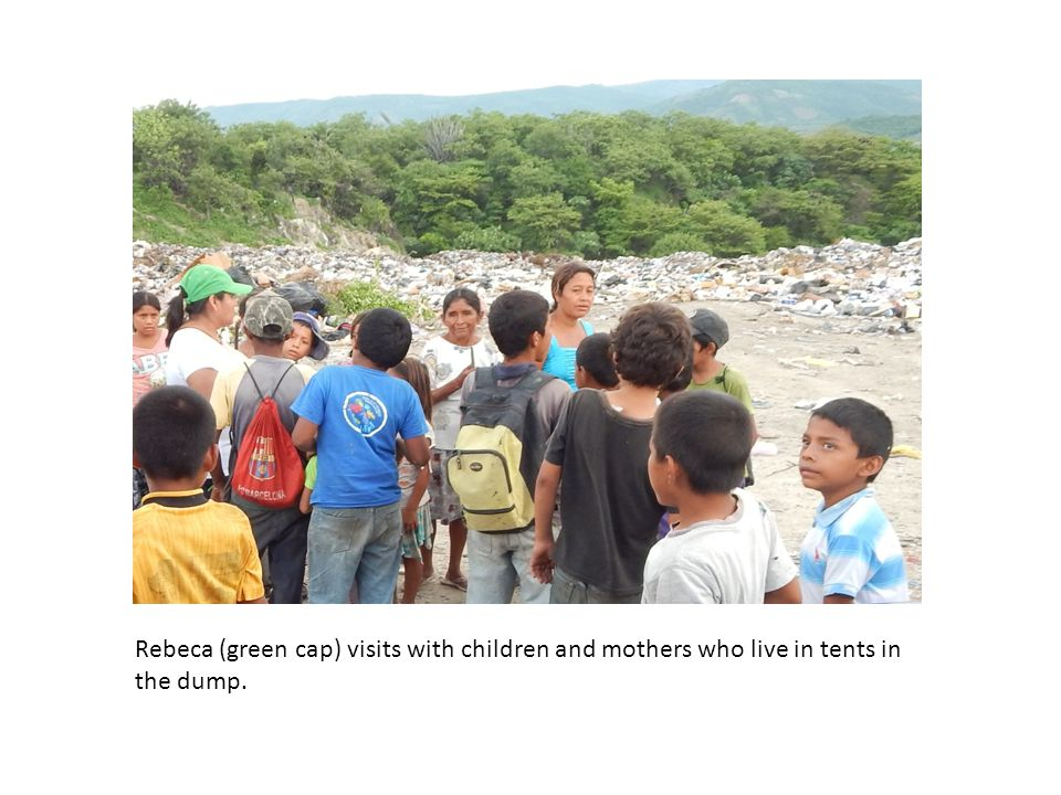 Rebeca (green cap) visits with children and mothers who live in tents in the dump.