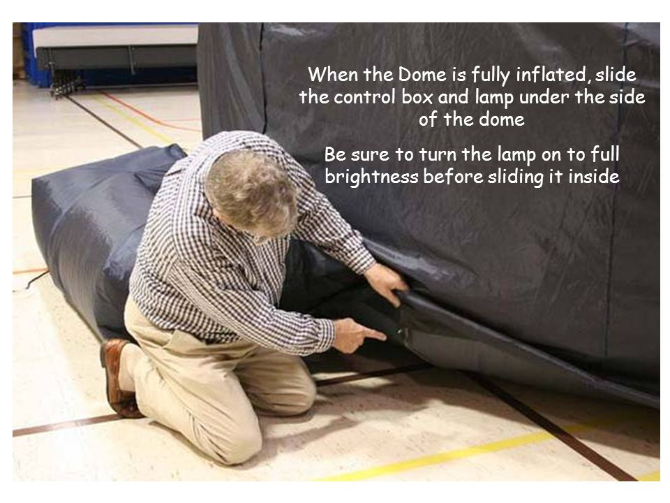 When the Dome is fully inflated, slide the control box and lamp under the side of the dome Be sure to turn the lamp on to full brightness before slidi