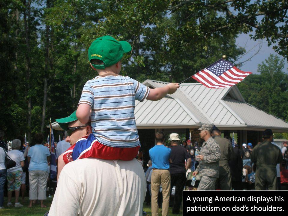 A young American displays his patriotism on dad's shoulders.