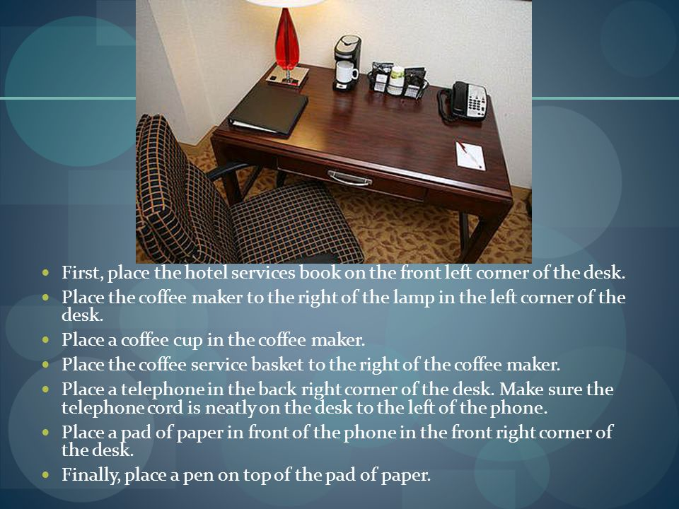 First, place the hotel services book on the front left corner of the desk.