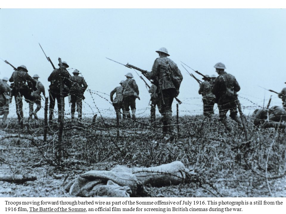 Troops moving forward through barbed wire as part of the Somme offensive of July 1916.