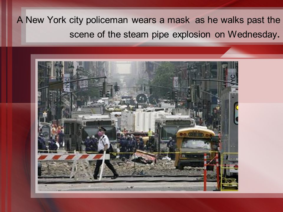 A New York city policeman wears a mask as he walks past the scene of the steam pipe explosion on Wednesday.