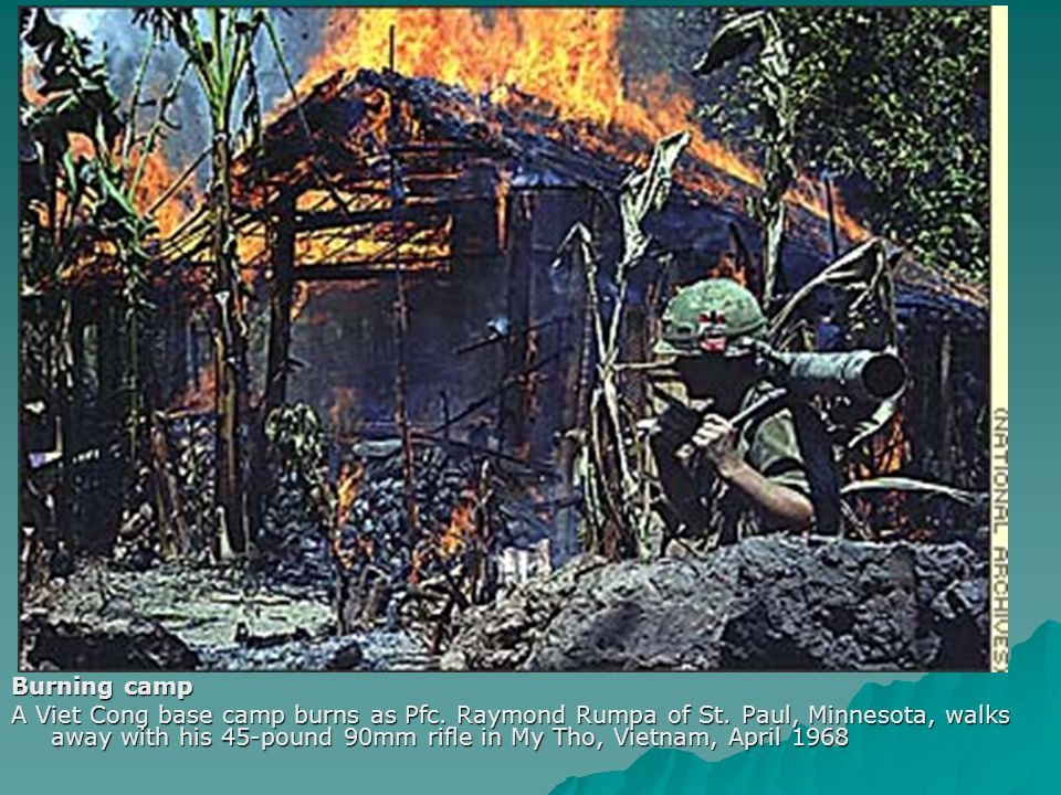 Burning camp A Viet Cong base camp burns as Pfc. Raymond Rumpa of St. Paul, Minnesota, walks away with his 45-pound 90mm rifle in My Tho, Vietnam, Apr