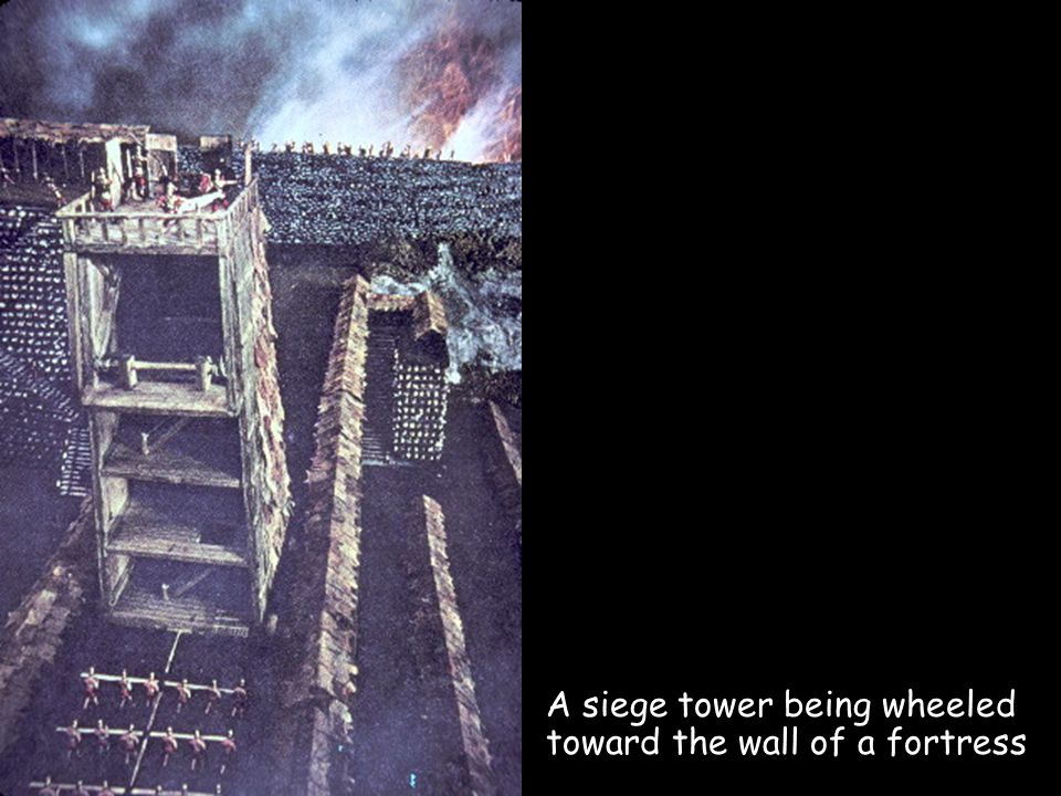 A siege tower being wheeled toward the wall of a fortress