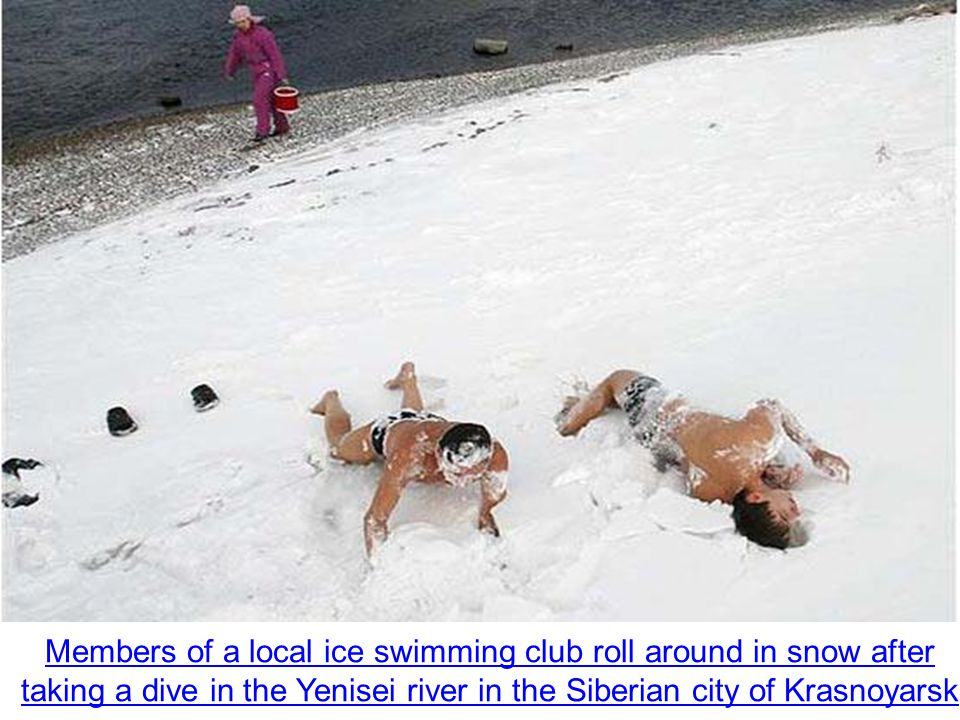 Members of a local ice swimming club roll around in snow after taking a dive in the Yenisei river in the Siberian city of Krasnoyarsk