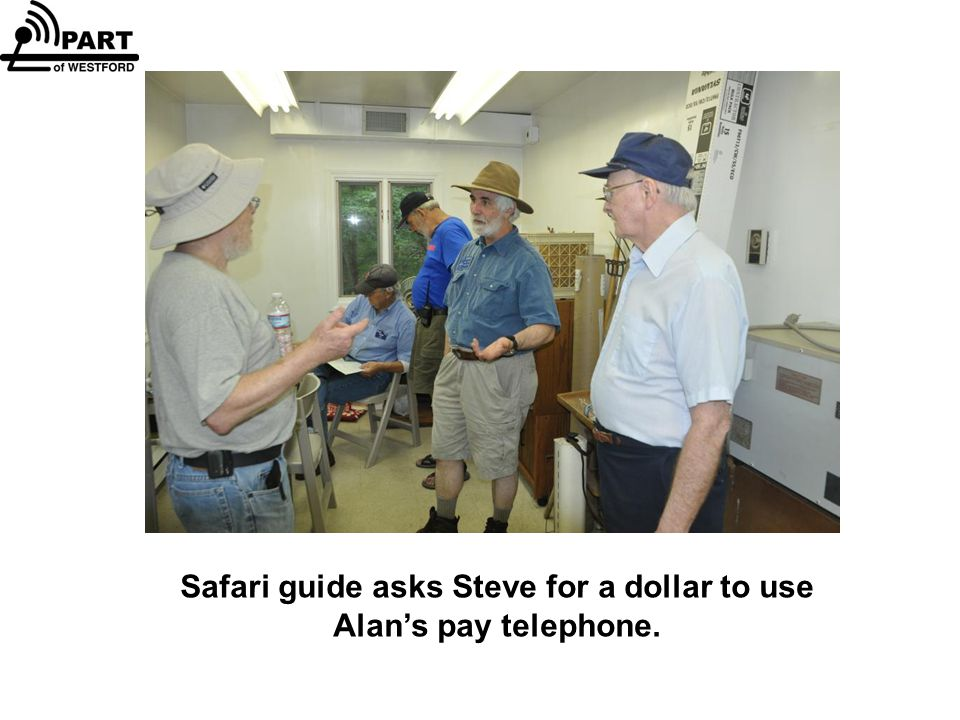 Safari guide asks Steve for a dollar to use Alan's pay telephone.