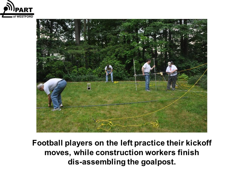 Football players on the left practice their kickoff moves, while construction workers finish dis-assembling the goalpost.