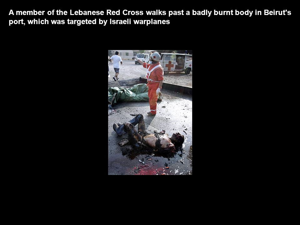 A member of the Lebanese Red Cross walks past a badly burnt body in Beirut s port, which was targeted by Israeli warplanes