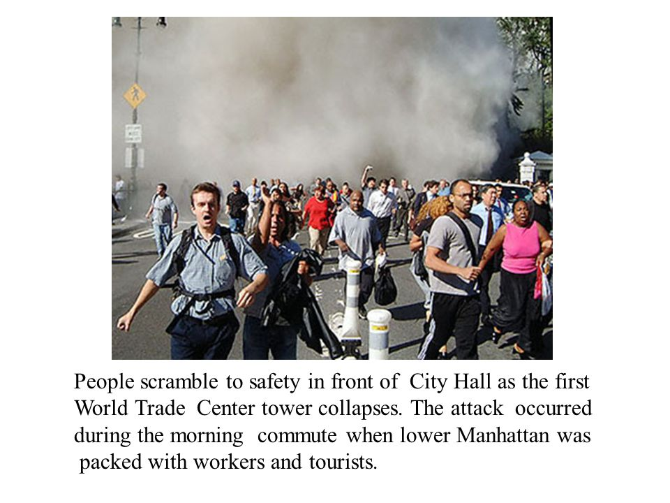 People scramble to safety in front of City Hall as the first World Trade Center tower collapses.