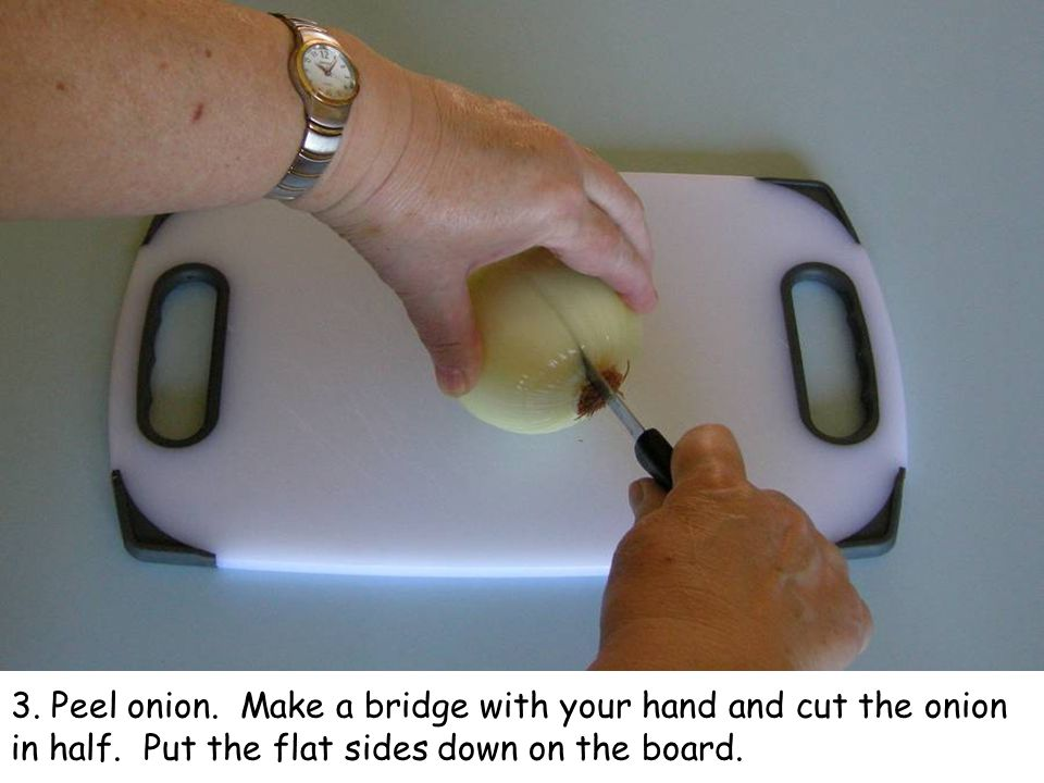 3. Peel onion. Make a bridge with your hand and cut the onion in half. Put the flat sides down on the board.