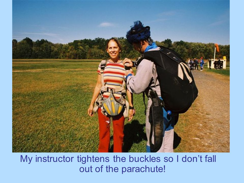 My instructor tightens the buckles so I don't fall out of the parachute!
