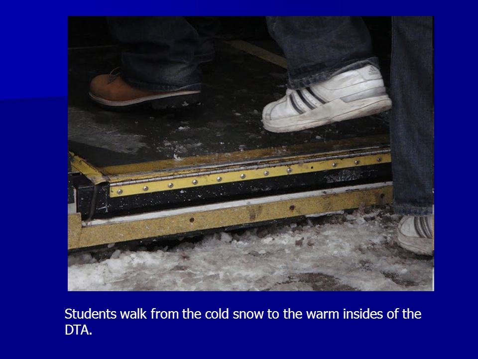 Students walk from the cold snow to the warm insides of the DTA.