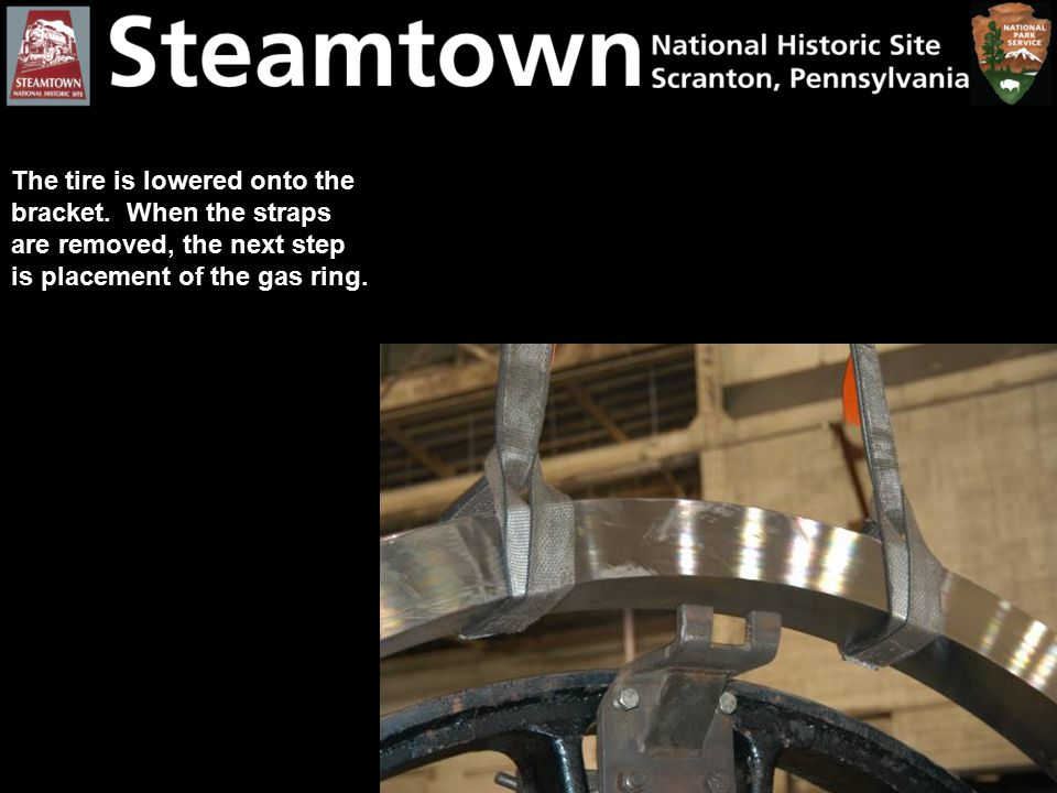 The tire is lowered onto the bracket. When the straps are removed, the next step is placement of the gas ring.