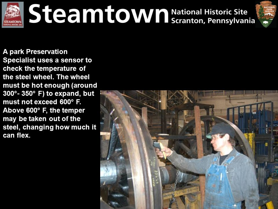 A park Preservation Specialist uses a sensor to check the temperature of the steel wheel. The wheel must be hot enough (around 300°- 350° F) to expand