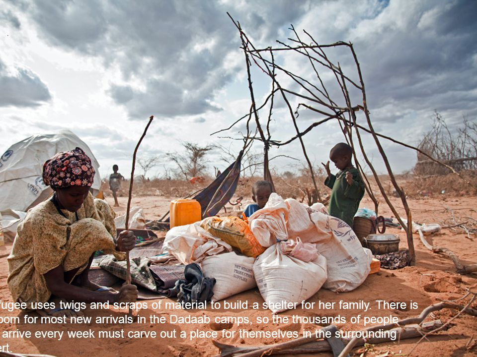 A refugee uses twigs and scraps of material to build a shelter for her family.
