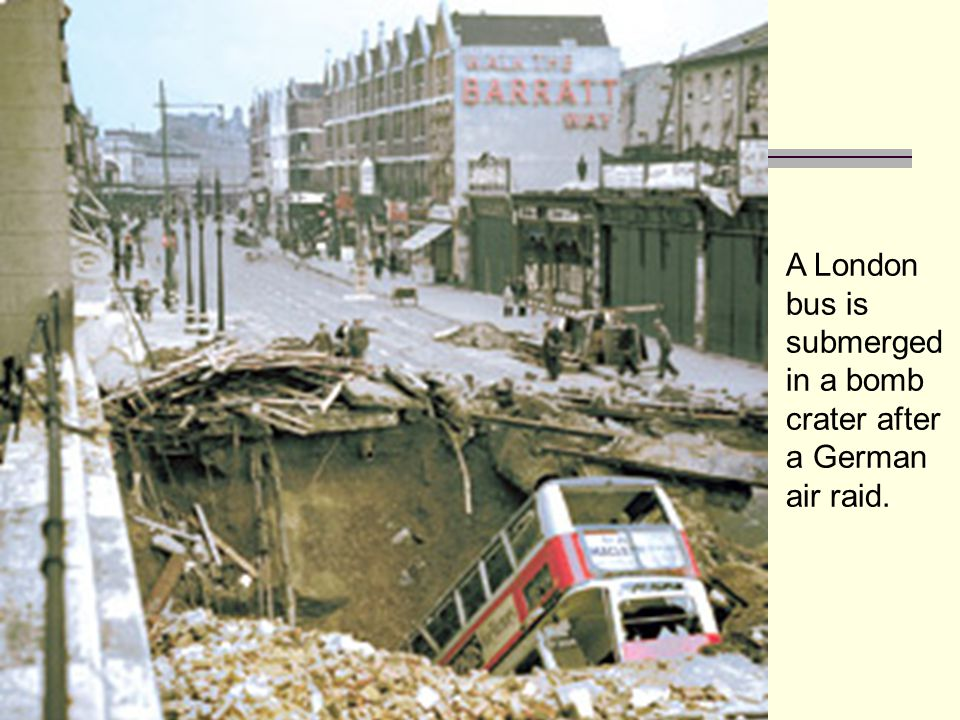 A London bus is submerged in a bomb crater after a German air raid.
