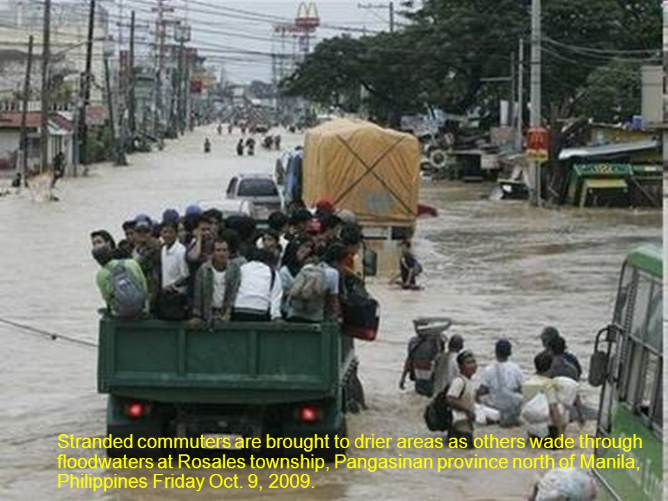 Residents struggle from raging floodwaters at Rosales township, Pangasinan province north of Manila, Philippines Friday Oct.9, 2009.