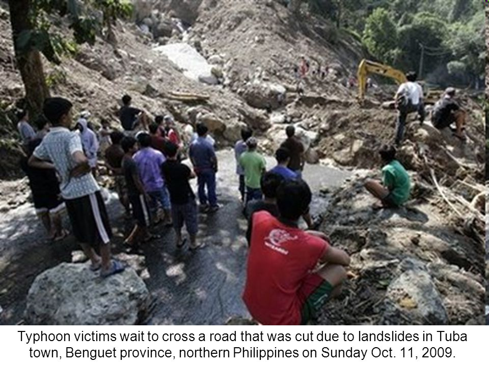 Filipino police officers bring down a body they recovered from landslides in the village of Puguis, La Trinidad town, Benguet province, northern Phili