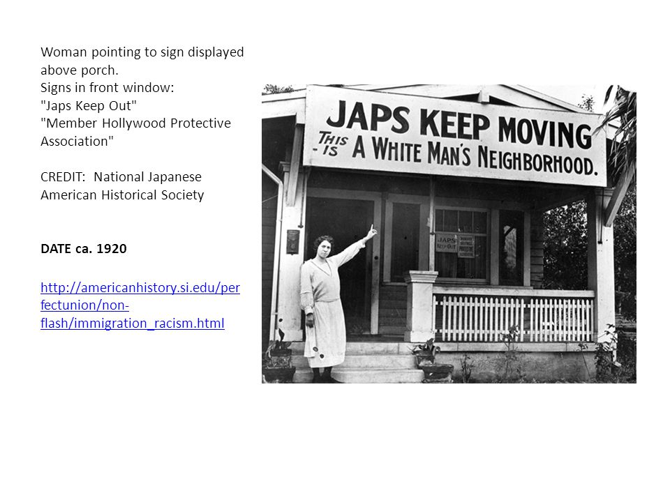 Woman pointing to sign displayed above porch. Signs in front window: