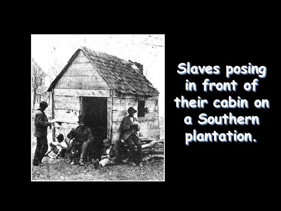 Slaves posing in front of their cabin on a Southern plantation.