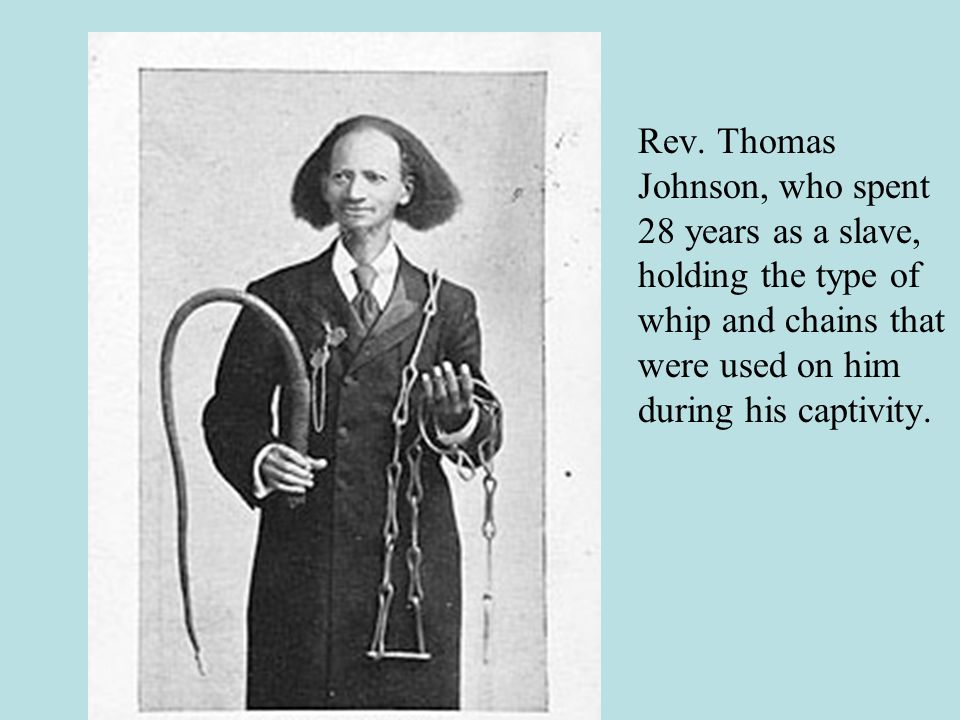 Rev. Thomas Johnson, who spent 28 years as a slave, holding the type of whip and chains that were used on him during his captivity.