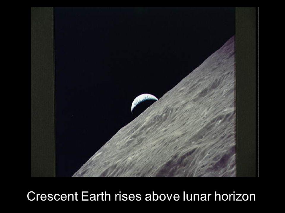 Crescent Earth rises above lunar horizon