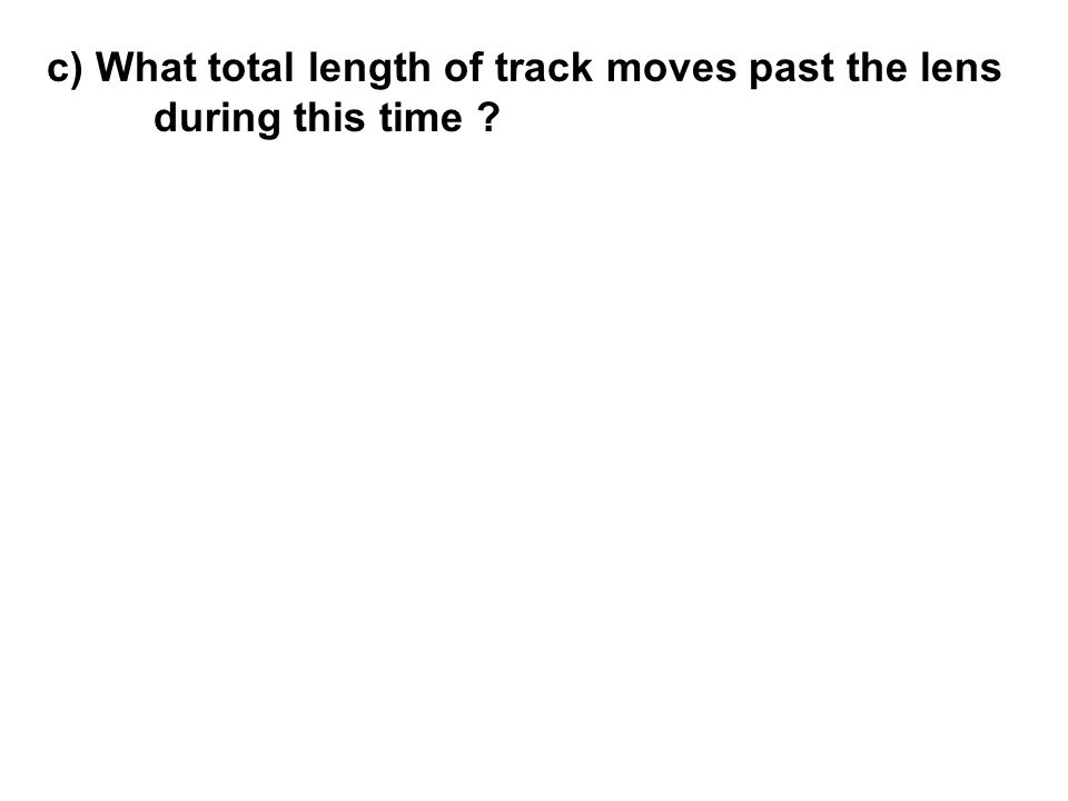 c) What total length of track moves past the lens during this time ?